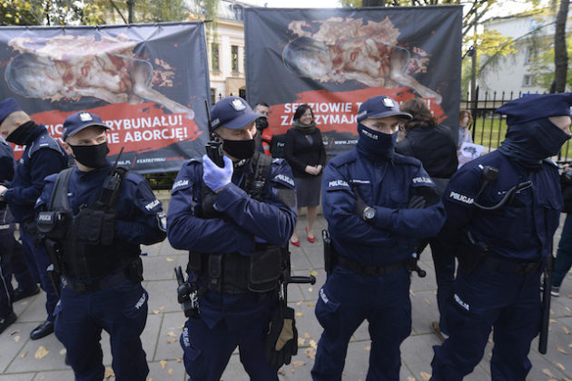 Police guard Poland's constitutional court as pro-choice and anti-abortion activists protest, in Warsaw, Poland, Thursday, Oct. 22, 2020. Poland's top court has ruled that a law allowing abortion of fetuses with congenital defects is unconstitutional. The decision by the country's Constitutional Court effectively bans terminating pregnancies in cases where birth defects are found and will further limit access to abortions in Poland. (AP Photo/Czarek Sokolowski)